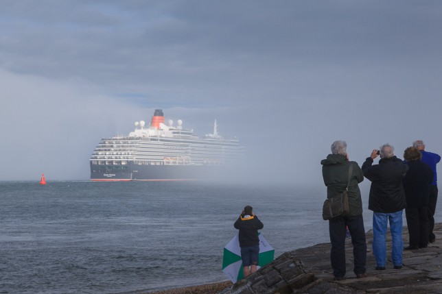 Bystanders at Calshot Castle watch as Queen Victoria disappears into sea fog on Southampton Water.