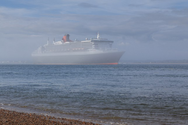 Queen Mary 2 emerges from fog on Southampton Water as she passes Calshot Castle.