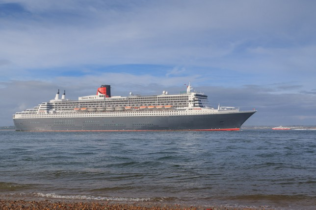 Queen Mary 2 passes the Red Jet Isle of Wight fast ferry on Southampton Water, near Calshot Castle.
