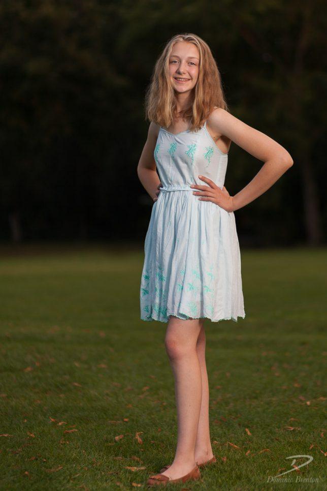 Full-length portrait of a blonde teenage girl in a light blue dress, smiling.