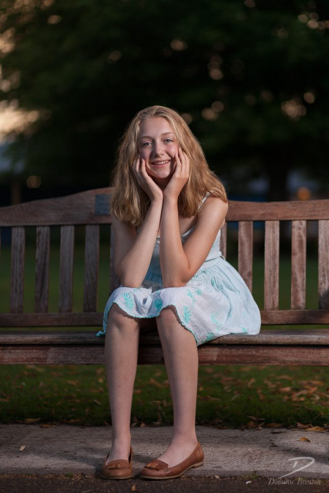 Blonde teenage girl in a light blue dress, sitting on a park bench, cradling her head with her hands.