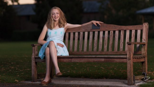 Blonde teenage girl in a light blue dress, sitting at one end of a park bench at sunset.