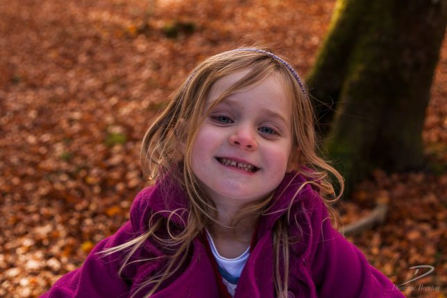 Little blonde girl in a pink coat looking up and smiling in the New Forest