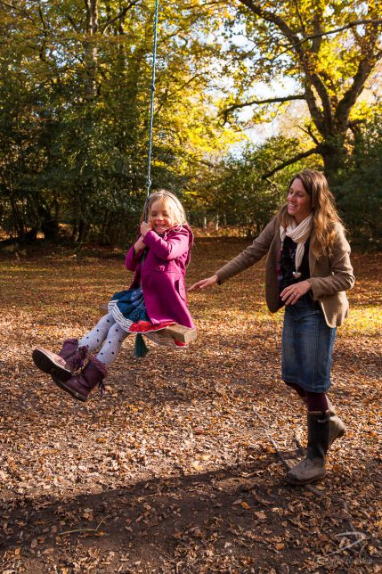 Young blonde girl in a pink coat on a rope swing in the New Forest being pushed by her mother