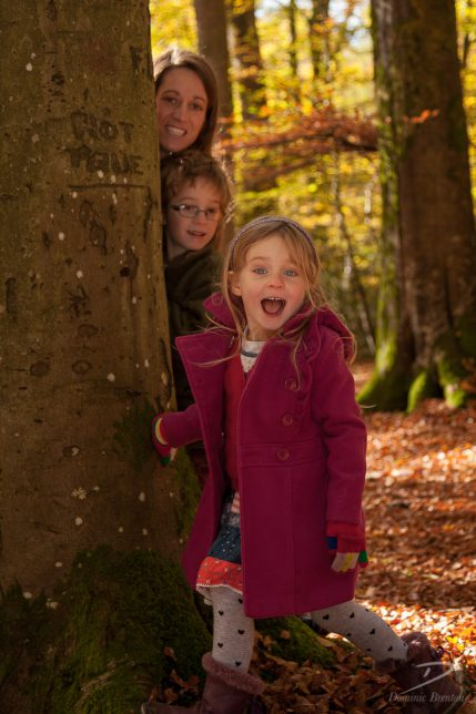 Mother, son and excited daughter peering around a tree in the New Forest