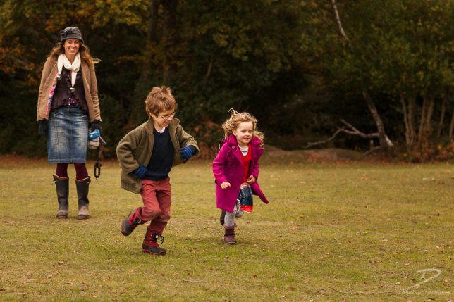 Young boy with glasses and young girl with blonde hair and pink coat running across a village green. Their mother is smiling in the background