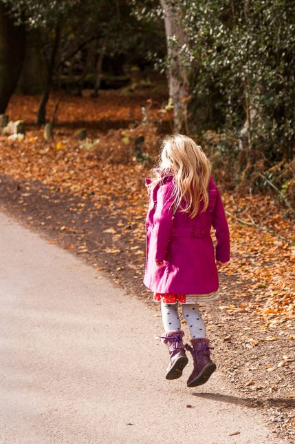Young girl with long blonde hair in pink coat skipping along a New Forest road