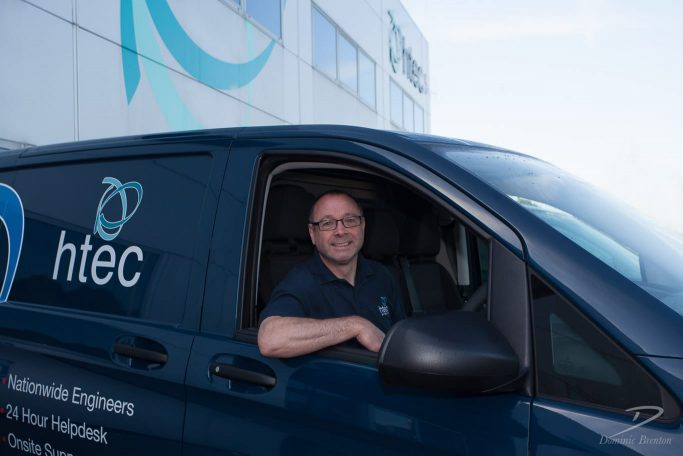 Smiling man at wheel of HTEC-branded van outside HTEC office