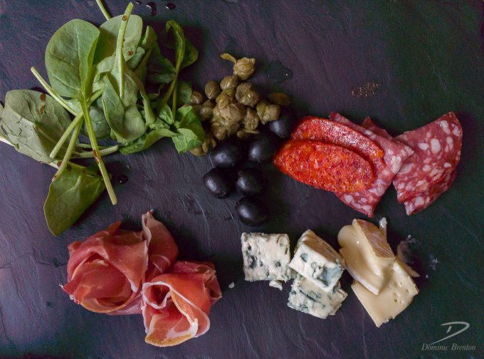 Salami, parma ham, cheese, olives and watercress on a slate board