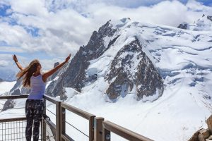 Girl with arms raised facing snowy mountain