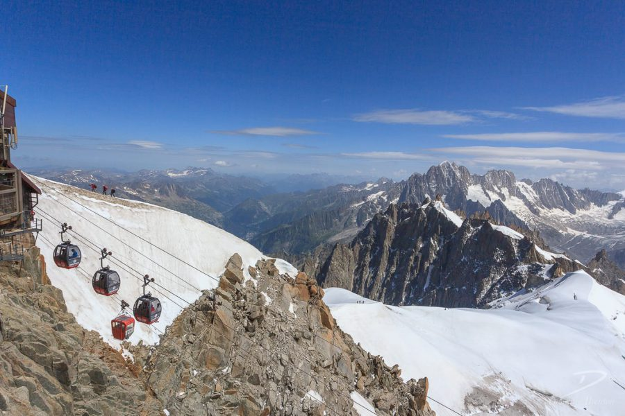 Rocky mountain summit, with three cable car gondolas between gap in rocks