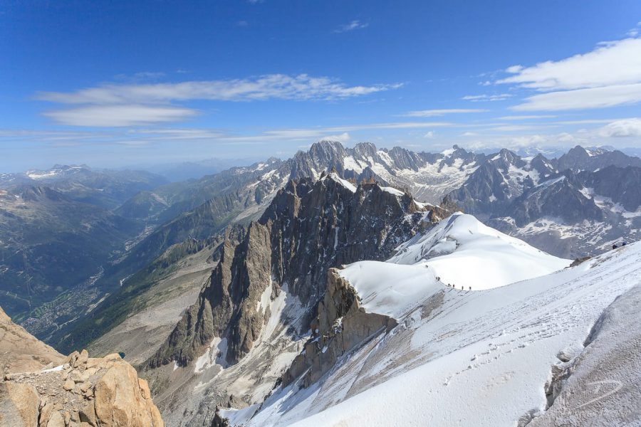 People on distant snowy ridge with rugged mountain backdrop