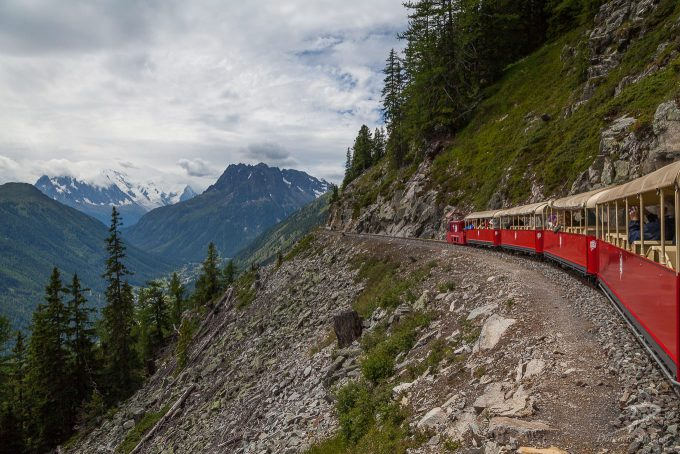 Miniature train with red carriages on the side of a mountain