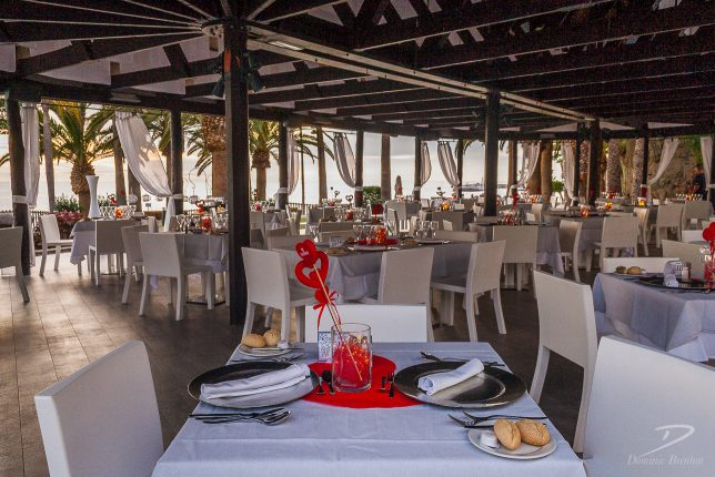Tables in outside restaurant with red table decorations