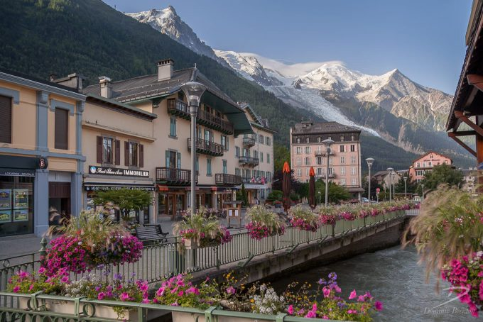 Flowers adorn railings above the River Arve in Chamonix, with Mont Blanc in the background.