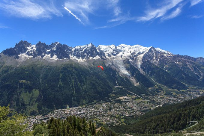 Mont Blanc massif under clear blue skies with red paraglider beneath
