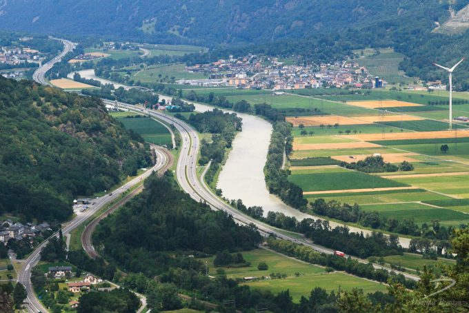 Roads, a railway line and a wide river form s-curves in a valley