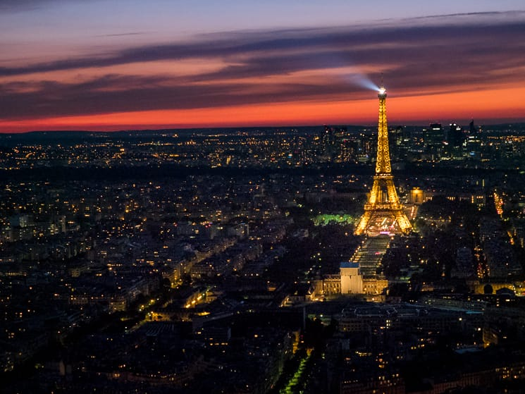 Searchlight shining from the Eiffel Tower over Paris at dusk
