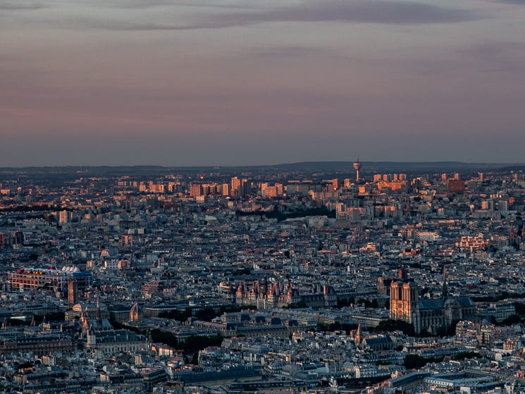 The skyline of Paris from the Tour Montparnasse bathed in a pink sunset glow